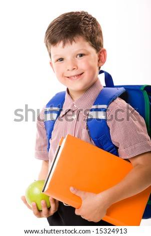 Portrait of smiling schoolboy with rucksack holding book and apple
