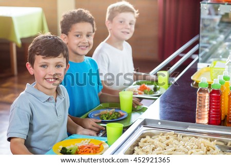 Portrait of smiling schoolboys standing near counter of school canteen - stock photo