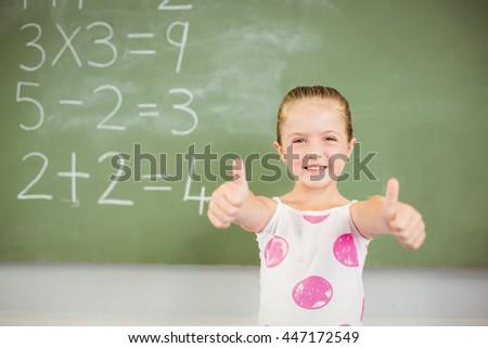 Portrait of smiling schoolgirl showing thumbs up in classroom at school - stock photo