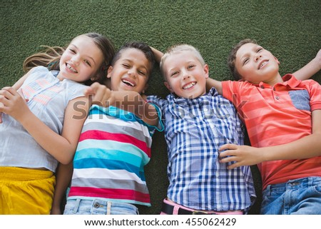 Portrait of smiling schoolkids lying on grass in campus at school - stock photo