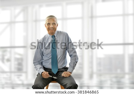 Portrait of smiling senior businessman sitting on a stool against office window background while looking at camera. - stock photo
