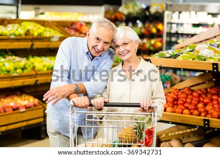 Portrait of smiling senior couple at the grocery shop - stock photo