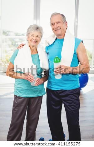 Portrait of smiling senior couple holding bottle while exercising - stock photo