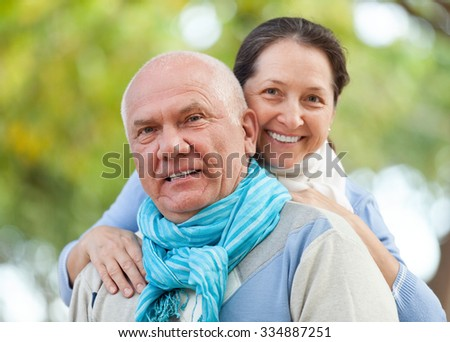 Portrait of smiling senior couple in sweaters at autumn park - stock photo