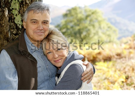 Portrait of smiling senior couple leaning against tree - stock photo