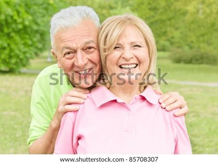 Portrait of smiling senior couple outdoors. - stock photo