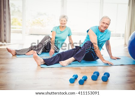 Portrait of smiling senior couple performing yoga at home - stock photo