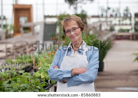 Portrait of smiling senior female worker standing with arms crossed - stock photo