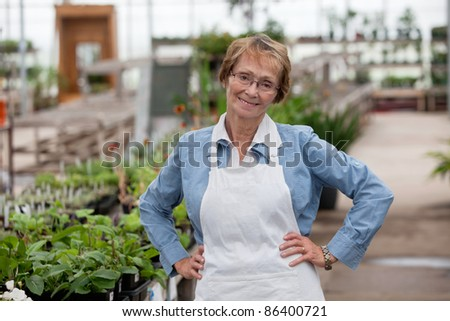 Portrait of smiling senior female worker standing with hands on hip - stock photo