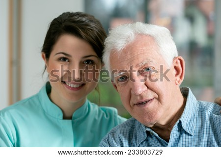 Portrait of smiling senior man and young nurse - stock photo