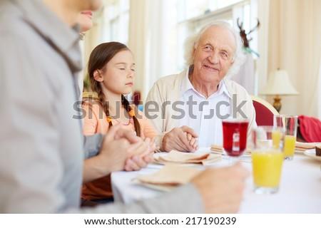 Portrait of smiling senior man at festive table during pray - stock photo