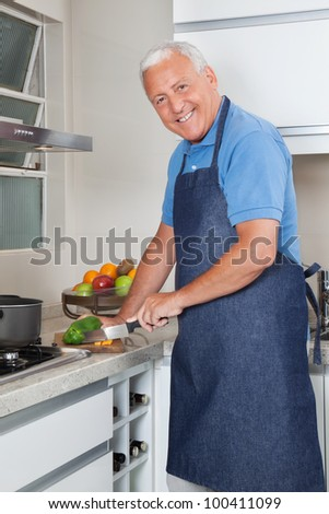 Portrait of smiling senior man cutting vegetables at kitchen counter - stock photo