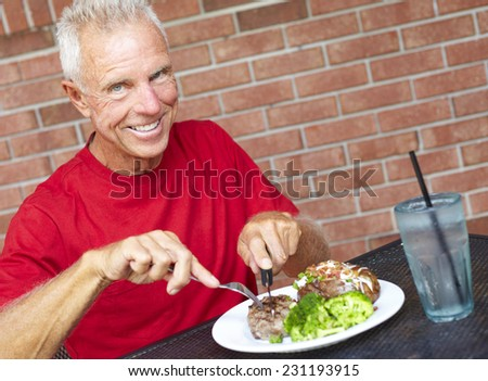 Portrait of smiling senior man eating strip steak served with loaded baked potato and broccoli at restaurant table - stock photo
