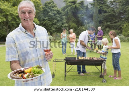 Portrait of smiling senior man holding plate of barbecue and wine with family in background - stock photo