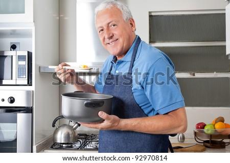 Portrait of smiling senior man holding spoon to taste food - stock photo