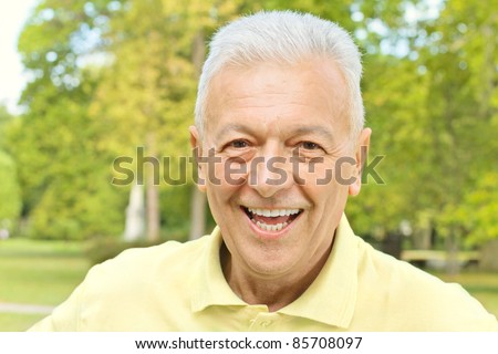 Portrait of smiling senior man in the park. - stock photo