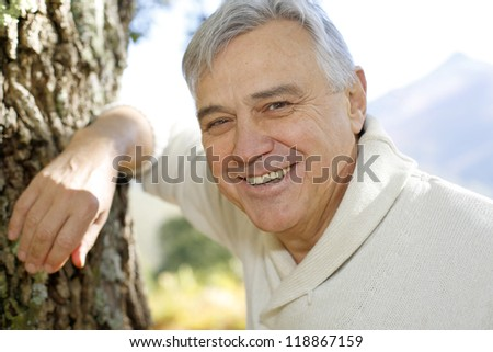 Portrait of smiling senior man leaning against tree - stock photo