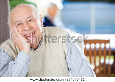 Portrait of smiling senior man sitting at nursing home with grandson in background - stock photo