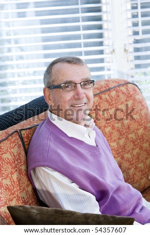 Portrait of smiling senior man sitting on living room couch