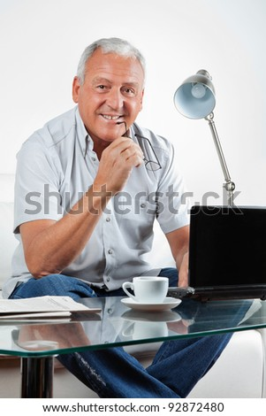 Portrait of smiling senior man sitting with laptop on table at home - stock photo