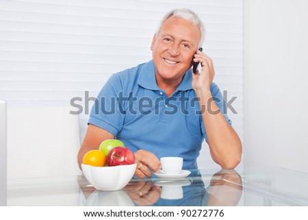 Portrait of smiling senior man talking on cell phone while having tea - stock photo