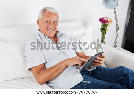 Portrait of smiling senior man using digital tablet PC - stock photo