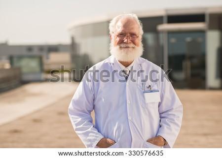 Portrait of smiling senior scientist in lab coat - stock photo