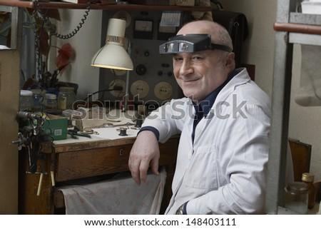Portrait of smiling senior watch repairman in workshop - stock photo