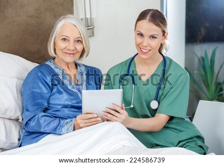 Portrait of smiling senior woman and female caretaker holding tablet PC in bedroom at nursing home - stock photo