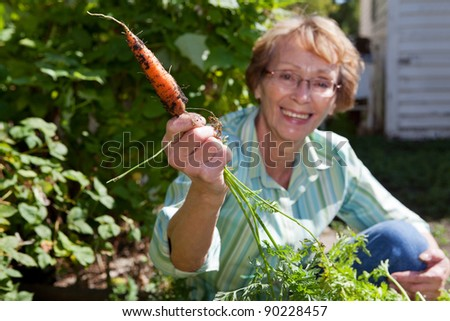 Portrait of smiling senior woman holding carrot - stock photo