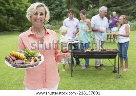 Portrait of smiling senior woman holding plate of barbecue and wine with family in background - stock photo