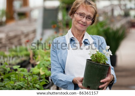 Portrait of smiling senior woman holding potted plant