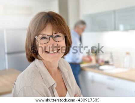 Portrait of smiling senior woman, husband in background - stock photo