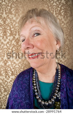 Portrait of smiling senior woman in front of gold background