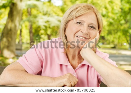 Portrait of smiling senior woman in the park. - stock photo
