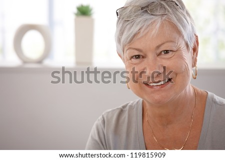 Portrait of smiling senior woman, looking at camera. - stock photo