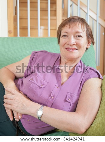 Portrait of smiling senior woman relaxing on couch at home - stock photo
