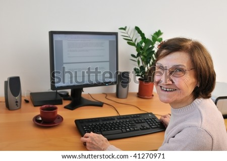 Portrait of smiling senior woman sitting at computer - stock photo