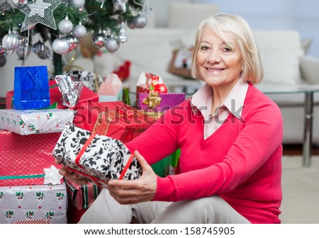 Portrait of smiling senior woman sitting by stack of Christmas presents at home - stock photo