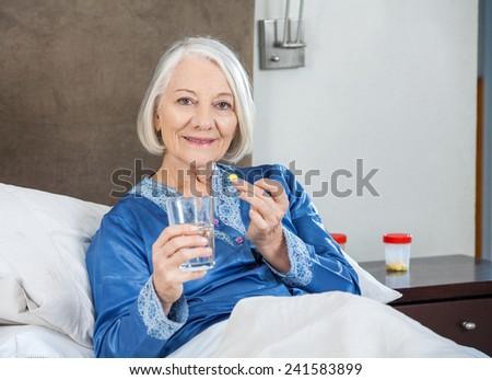 Portrait of smiling senior woman taking medicine on bed at nursing home - stock photo