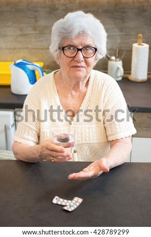 Portrait of smiling senior woman taking pills and holding a glass of water at home. - stock photo