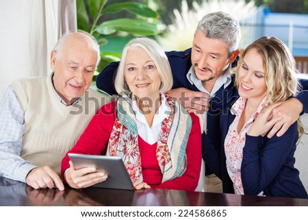 Portrait of smiling senior woman using digital tablet with family at nursing home - stock photo