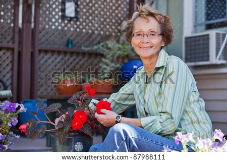 Portrait of smiling senior woman with potted plant - stock photo