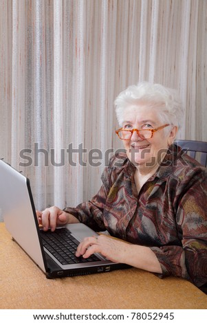 Portrait of smiling senior woman working at computer - stock photo