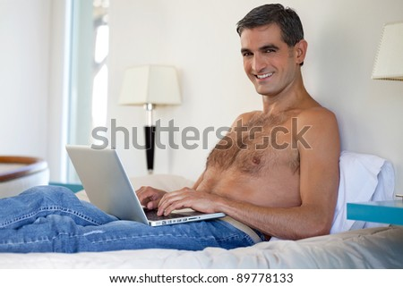 Portrait of smiling shirtless middle aged man working on laptop - stock photo