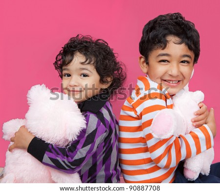 Portrait of Smiling Siblings Clutching Their Stuffed Toys - stock photo