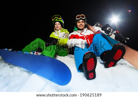 Portrait of smiling snowboarders at night - stock photo