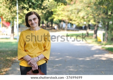 "Portrait of smiling ""80 something"" senior woman outdoors in park - stock photo"