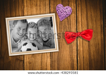 Portrait of smiling son, father and grandfather on floor against wooden table - stock photo