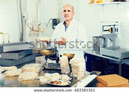 Portrait of smiling spanish mature male with packing of turron in food factory